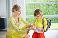 Woman preparing her daughter for school (thumbnail)