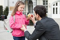 Man giving an apple to his daughter