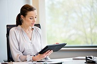 Businesswoman using a digital tablet in an office (thumbnail)