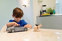 Boy playing with a toy car