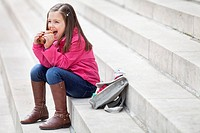 Schoolgirl sitting on the steps and eating pain au chocolat