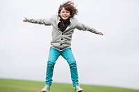 Portrait of a boy jumping in a field