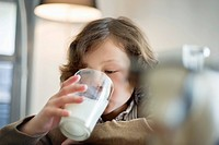 Close_up of a boy drinking a glass of milk
