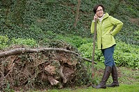 Woman standing with a shovel near a heap of rubbish