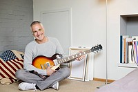 Portrait of a happy man playing a guitar