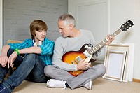Man playing a guitar with his son at home