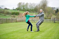 Man playing with his daughter in a field