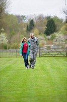 Man walking with his daughter in a field