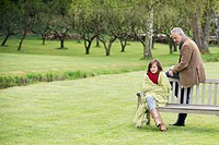 Man sitting with his daughter on a bench in a park