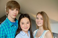 Portrait of a teenage boy with his two sisters smiling