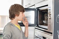 Teenage boy looking into an oven with surprise