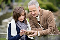 Man with his daughter holding a bird's nest in a park