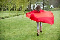 Girl running in a field with a blanket (thumbnail)