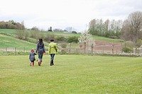 Girl walking with her mother and grandmother in a lawn