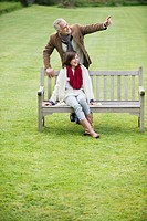 Man sitting with his daughter on a bench and pointing in a park