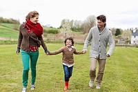 Happy family walking in a field