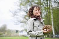 Portrait of a boy holding a bird's nest in a park (thumbnail)
