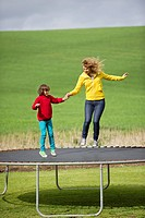 Woman with her son jumping on a trampoline in a field (thumbnail)