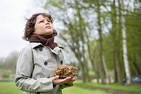 Close_up of a boy holding a bird's nest in a park