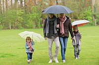 Family walking with umbrellas in a park