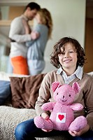 Boy sitting with a toy with his parents romancing in the background