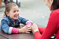 Girl sitting with her mother at a sidewalk cafe