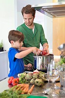 Boy assisting his father in the kitchen
