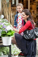 Woman and her daughter looking at flowers in a flower shop