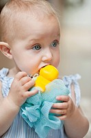 Close_up of a baby girl playing with a toy
