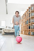 Woman playing with her daughter walking towards a ball