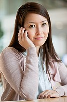 Portrait of a businesswoman talking on a mobile phone in an office (thumbnail)