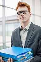 Portrait of a businessman holding files in an office