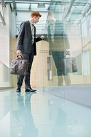 Businessman peeking through glass in a corridor