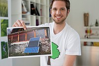 Man showing an ecological poster of solar panel (thumbnail)