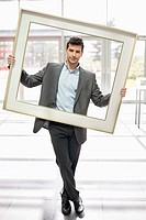Businessman holding a frame in an office lobby