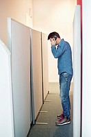 Businessman talking on a mobile phone in an office corridor