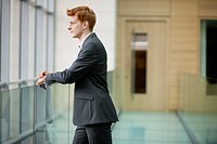 Businessman looking through glass window in a corridor (thumbnail)