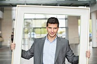 Close_up of a businessman holding a frame in an office lobby