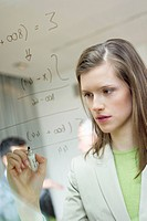 Businesswoman writing numeric figures on a glass surface (thumbnail)