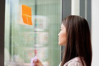Businesswoman sticking memo notes on glass in an office (thumbnail)