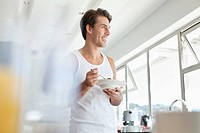 Smiling man eating cereal in kitchen (thumbnail)