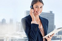 Portrait of smiling woman holding digital tablet and talking on cell phone (thumbnail)