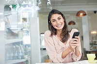 Portrait of smiling woman holding cell phone in café window