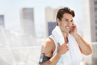 Smiling man with mp3 player on sunny, urban balcony