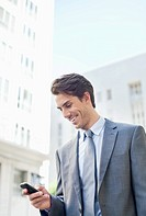 Smiling businessman checking cell phone