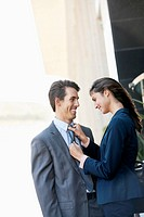 Smiling businesswoman adjusting businessman's tie