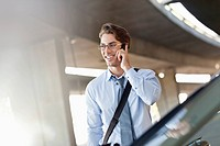Smiling businessman talking on cell phone in parking garage