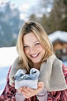 Portrait of smiling woman holding Christmas gift in snow