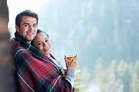 Portrait of smiling couple wrapped in a blanket and drinking hot cider on porch