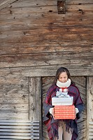 Portrait of smiling woman holding Christmas gifts in front of cabin